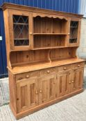 A modern pine dresser, the plate rack with two leaded glazed doors over four drawers and four twin