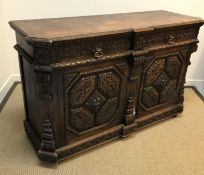 A late Victorian carved oak enclosed dresser in the Gothic Revival taste, the top with foliate
