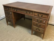 An early 20th Century mahogany double pedestal desk with three frieze drawers raised on two banks of