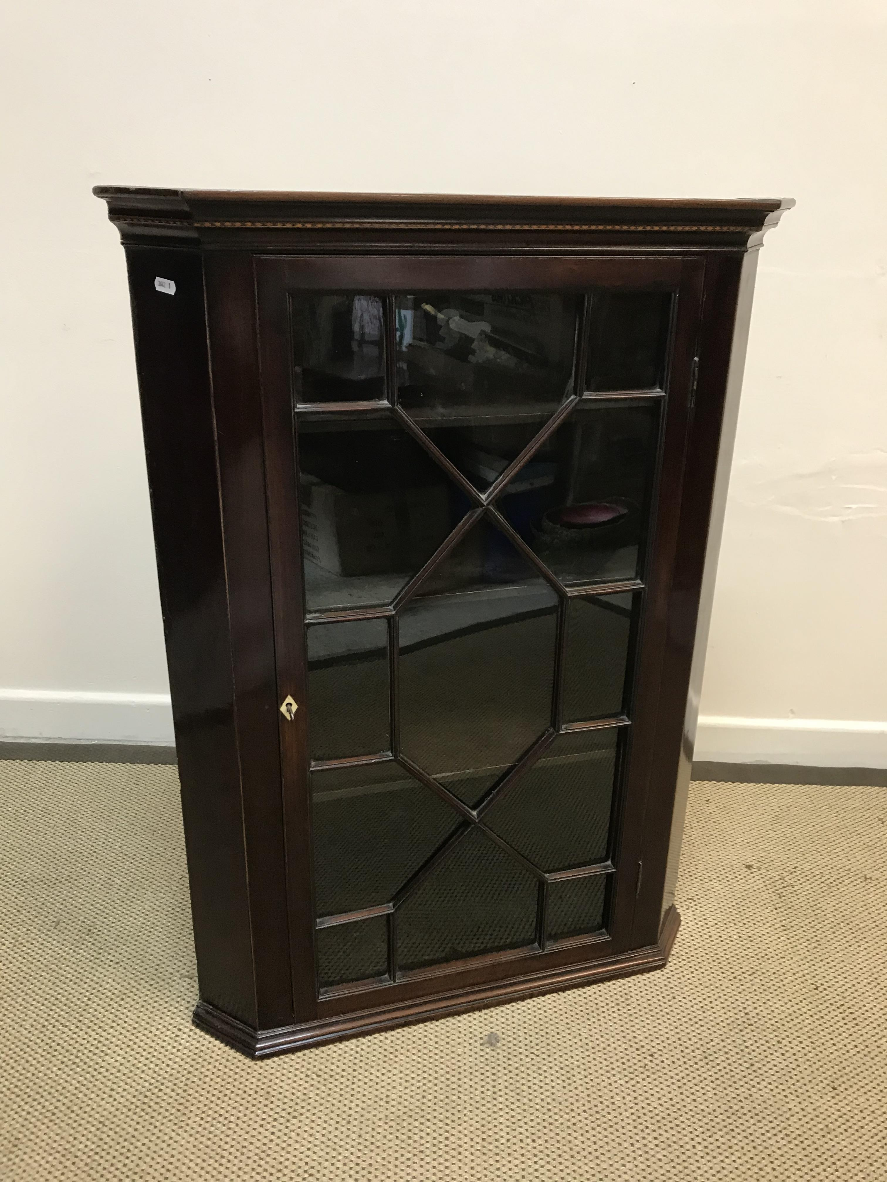 An early 19th Century mahogany hanging corner cabinet, the moulded cornice with lozenge inlaid