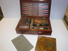 A mahogany cased games compendium containing various games pieces including Chess, Draughts,