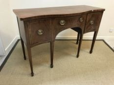 A 19th Century mahogany serpentine fronted sideboard with central drawer flanked by deep drawer