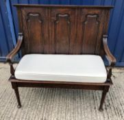 A late Victorian oak settle in the 18th Century manner, the three panel back on a plain plank seat