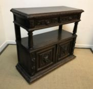 A Victorian carved oak buffet in the Gothic Revival taste, the plain top with lunette carved