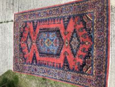 A Caucasian carpet, the central panel set with stylised flower head decorated medallion on a red and