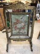 An early 19th Century carved giltwood and gesso framed fire screen, one side set with a needlework