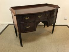 An Edwardian mahogany bow fronted sideboard, the plain top with cross-banded edging over two central