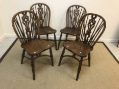 A set of four ash and elm stick back chairs in the 19th Century style, the shaped seats on turned
