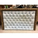 A 19th Century carved giltwood and gesso framed buttoned headboard with fruit and foliate decoration