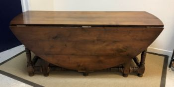 A 20th Century walnut oval double gate-leg dining table in the 18th Century manner, raised on turned