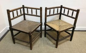 A pair of 19th Century stained beech framed bobbin turned corner chairs with rush seats, 43 cm x