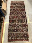 A fine Caucasian tribal carpet with repeating green, blue and red medallions, approx 246 cm x 102