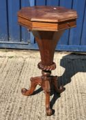 A Victorian rosewood work table of octagonal trumpet form, the top opening to reveal a fitted