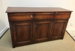 A modern cherry wood sideboard in the 19th Century Continental manner, the plain top with moulded