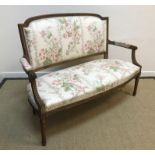 A circa 1900 carved walnut framed salon settee in the Louis XV taste, floral upholstered and