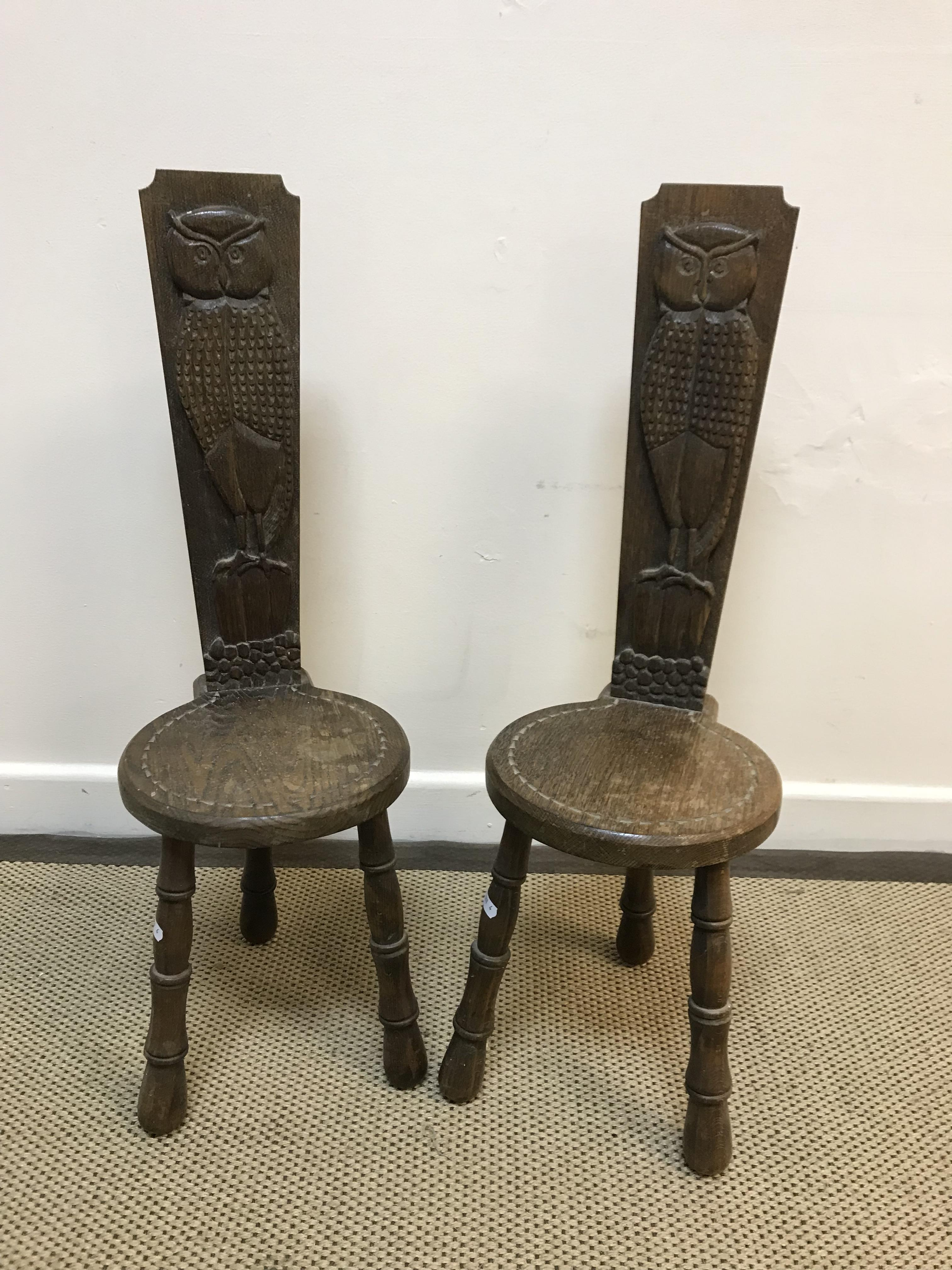 A pair of 20th Century oak spinning chairs, the backs carved with figures of owls upon a post,