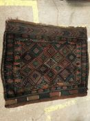 A Persian rug the central panel set with repeating diamond decoration on a dark ground, within a