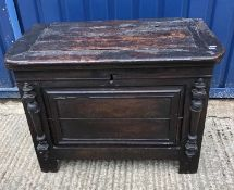 An oak coffer or chest, the plank top with pleated ends over a panelled front and sides with applied