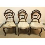 A set of five Victorian walnut standard salon chairs with upholstered seats on moulded cabriole