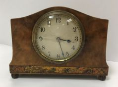 An early 20th Century French walnut cased mantel clock with chinoiserie banded decoration, raised on