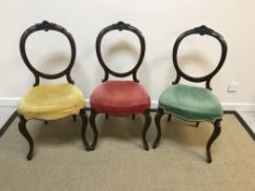 A set of three Victorian mahogany balloon back dining chairs with red, green and yellow velvet