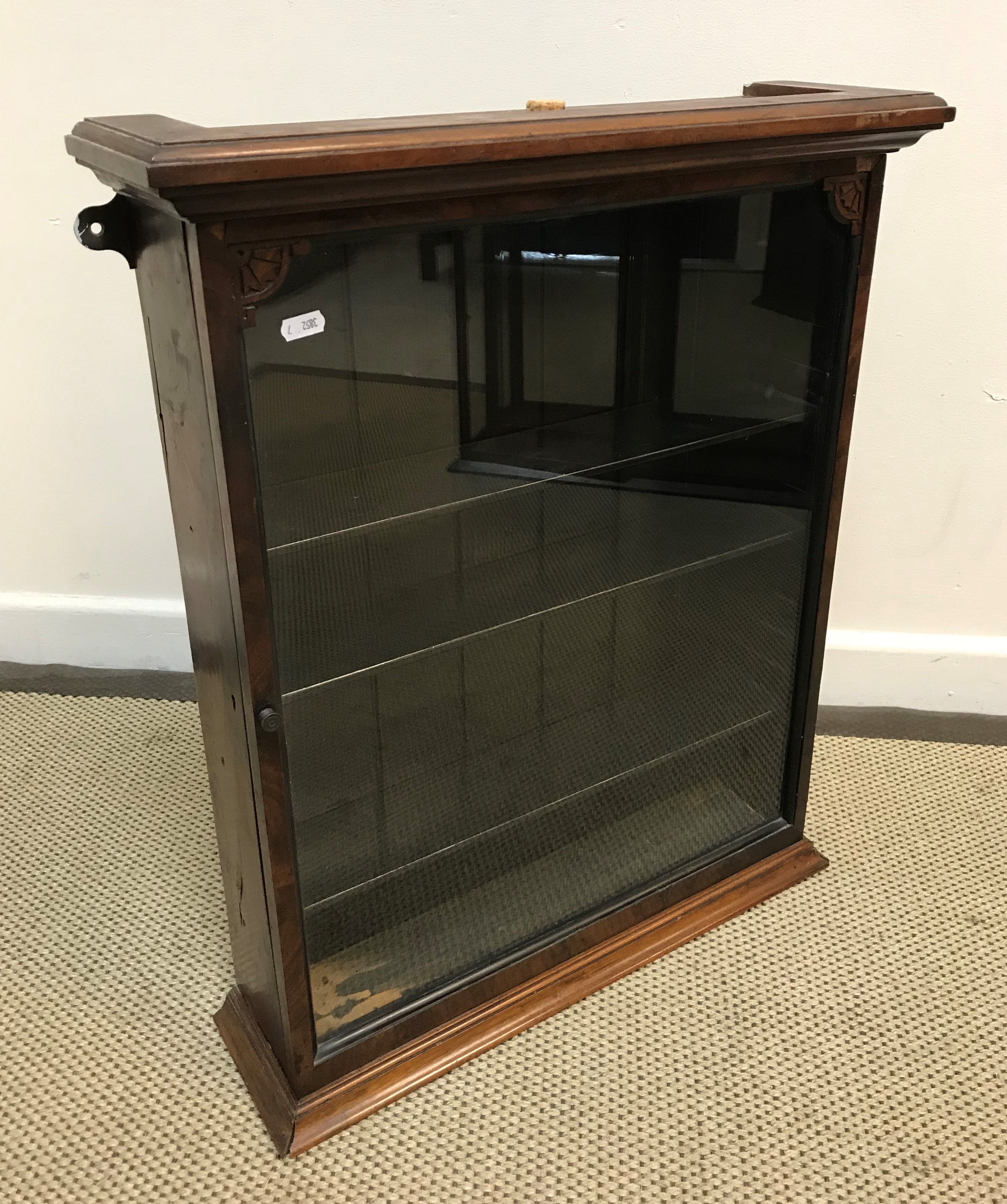 A late Victorian mahogany framed hanging wall cabinet with single glazed door enclosing adjustable