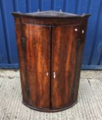 A 19th Century mahogany bow fronted corner cupboard, the two figured doors with ivory kite shaped