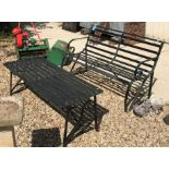 A wrought iron slatted two seat garden bench with scroll arms together with a similar slatted garden