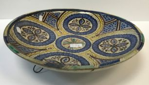 An Iznic type circular charger in blue and yellow with stylised floral design