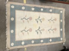 A modern rug, the central panel set with floral sprays on a cream ground, within a flower head