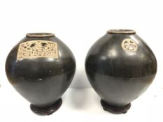 A pair of Oriental treacle glazed ovoid vases with panel / medallion decoration or simulated text,