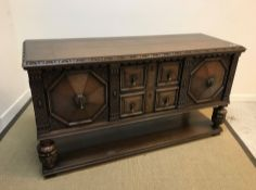 An early to mid 20th Century carved oak sideboard in the Elizabethan taste, the plain top with