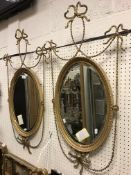 A pair of circa 1900 gilt and gesso framed oval wall mirrors with fine harebell drape and ribbon