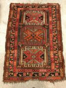 A Caucasian rug, the central panel set with three repeating medallions on a brown ground, within a