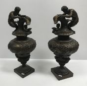 A pair of 19th Century patinated bronze ornamental ewers in the Classical taste, decorated with