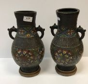 A pair of 19th Century Chinese bronze and cloisonné banded baluster shaped vases with kylin handles,