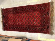 A Bokhara rug, the central panel set with repeating medallions on a dark red ground within stepped