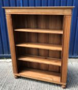 A modern teak open bookcase with three shelves flanked by fluted side columns on turned feet 112.5