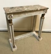 An Empire style pier table, the marble top over a plain frieze with wreath medallion carved ends,