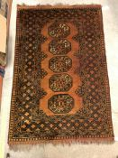 A Bokhara type rug set with repeating medallions on a burnt orange ground, within a stepped burnt