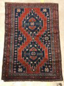 A Kasak rug, the central panel set with two repeating medallions on a red ground with stylised