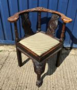 A 19th Century carved oak corner chair, the yoke back with mask decoration and dolphin carved splats