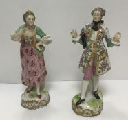 A pair of 19th Century Dresden figures in 18th Century dress, raised on scroll decorated bases,