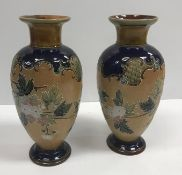 A pair of Doulton Lambeth relief work floral decorated vases with flared rims, 29.6 cm highCondition