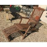 A modern slatted teak folding steamer chair with integral footrest and cushion