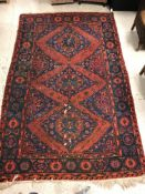 A Persian rug with three repeating lozenge medallions on a red and blue ground, within a blue, red