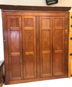 A mahogany cupboard / gun cabinet, the moulded cornice above two pairs of triple panelled doors