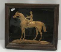 "A framed and glazed gilt brass and engraved cast figure of ""Jockey on horseback"", 36 cm x 26 cm"