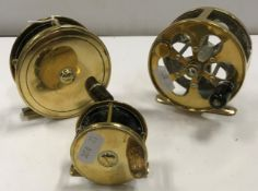 """A collection of three brass fly fishing reels to include an Army & Navy 31/4"""" plate wind reel, an"""