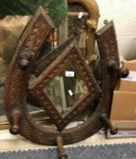 An early 20th Century carved oak wall mirror / coat hook in the form of a horse shoe, 69 cm x 56 cm
